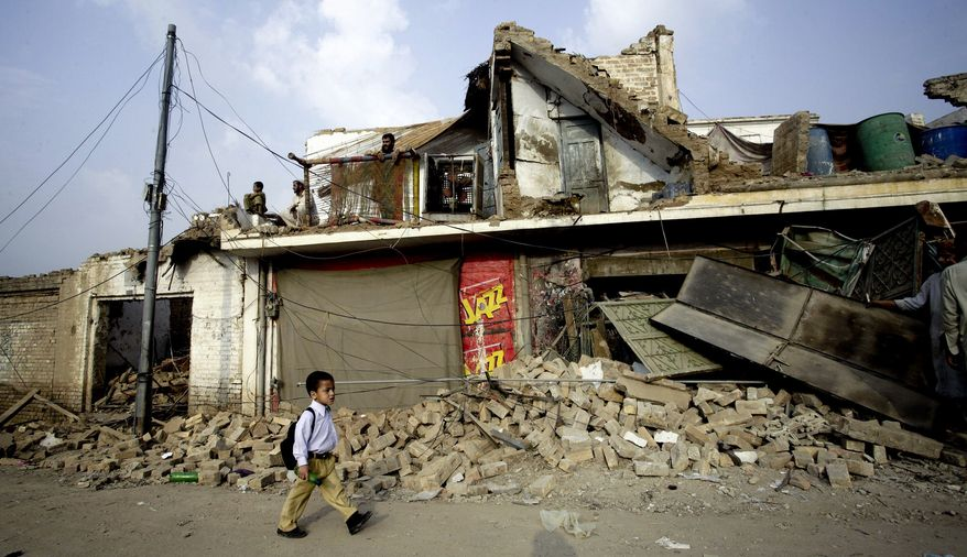 A Pakistani schoolchild walks past a building damaged in Tuesday night's car bombing in Kohat, 36 miles south of Peshawar, Pakistan. The bomb, which ripped through a police compound, killed 18 people, including 14 women and children and four officers, in the latest in a string of attacks proving that Islamist militants remain a potent force in the country. (AP Photo/Mohammad Sajjad)