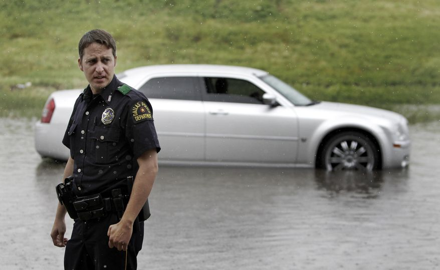 Dallas Police Officer David Meldrum turns around Wednesday after checking on a driver that stalled their car in water along the axis road of Interstate 35 in Dallas. The remnants of tropical storm Hermine moved through the area, causing minor flash flooding and road closures. (Associated Press)
