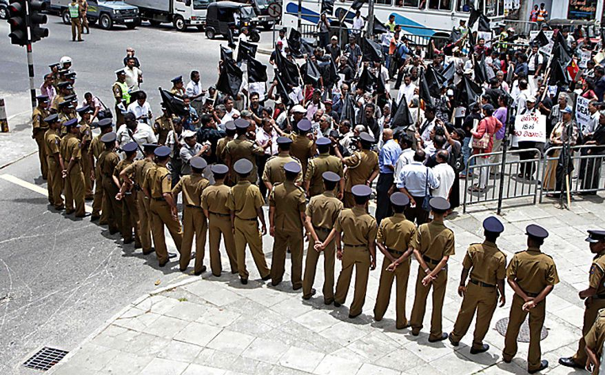 Sri Lankan opposition supporters are blocked by police during a protest in Colombo, Sri Lanka, Wednesday, Sept. 8, 2010. Sri Lanka's Parliament on Wednesday began debating a controversial amendment to the country's constitution that would allow President Mahinda Rajapaksa to hold unlimited number of terms, a move critics say could lead to a dictatorship. (AP Photo/Eranga Jayawardena)