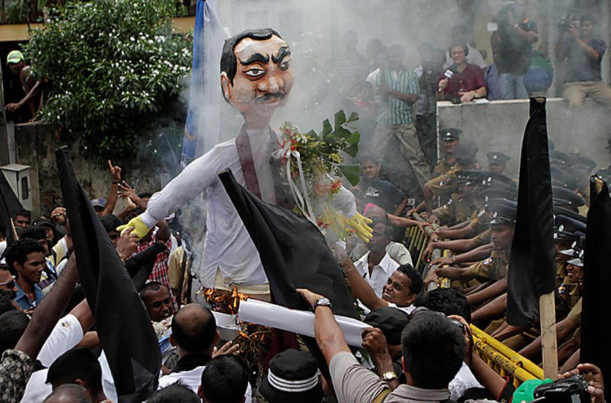 Sri Lankan opposition supporters burn an effigy of President Mahinda Rajapaksha as policemen block them during a protest in Colombo, Sri Lanka, Wednesday, Sept. 8, 2010. Sri Lanka's Parliament on Wednesday began debating a controversial amendment to the country's constitution that would allow President Mahinda Rajapaksa to hold unlimited number of terms, a move critics say could lead to a dictatorship. (AP Photo/Eranga Jayawardena)