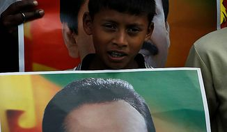 ** FILE ** A Sri Lankan boy supporting President Mahinda Rajapaksha holds his poster as they rally around the parliament complex in Colombo, Sri Lanka, Wednesday, Sept. 8, 2010. (AP Photo/Eranga Jayawardena)