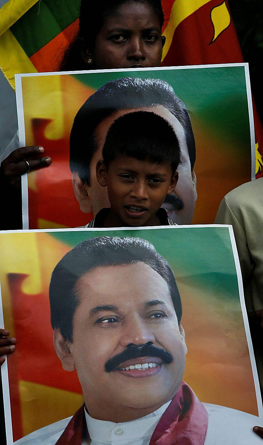 ** FILE ** A Sri Lankan boy supporting President Mahinda Rajapaksha holds his poster as they rally around the parliament complex in Colombo, Sri Lanka, Wednesday, Sept. 8, 2010. (AP Photo/Eranga Jayawardena)