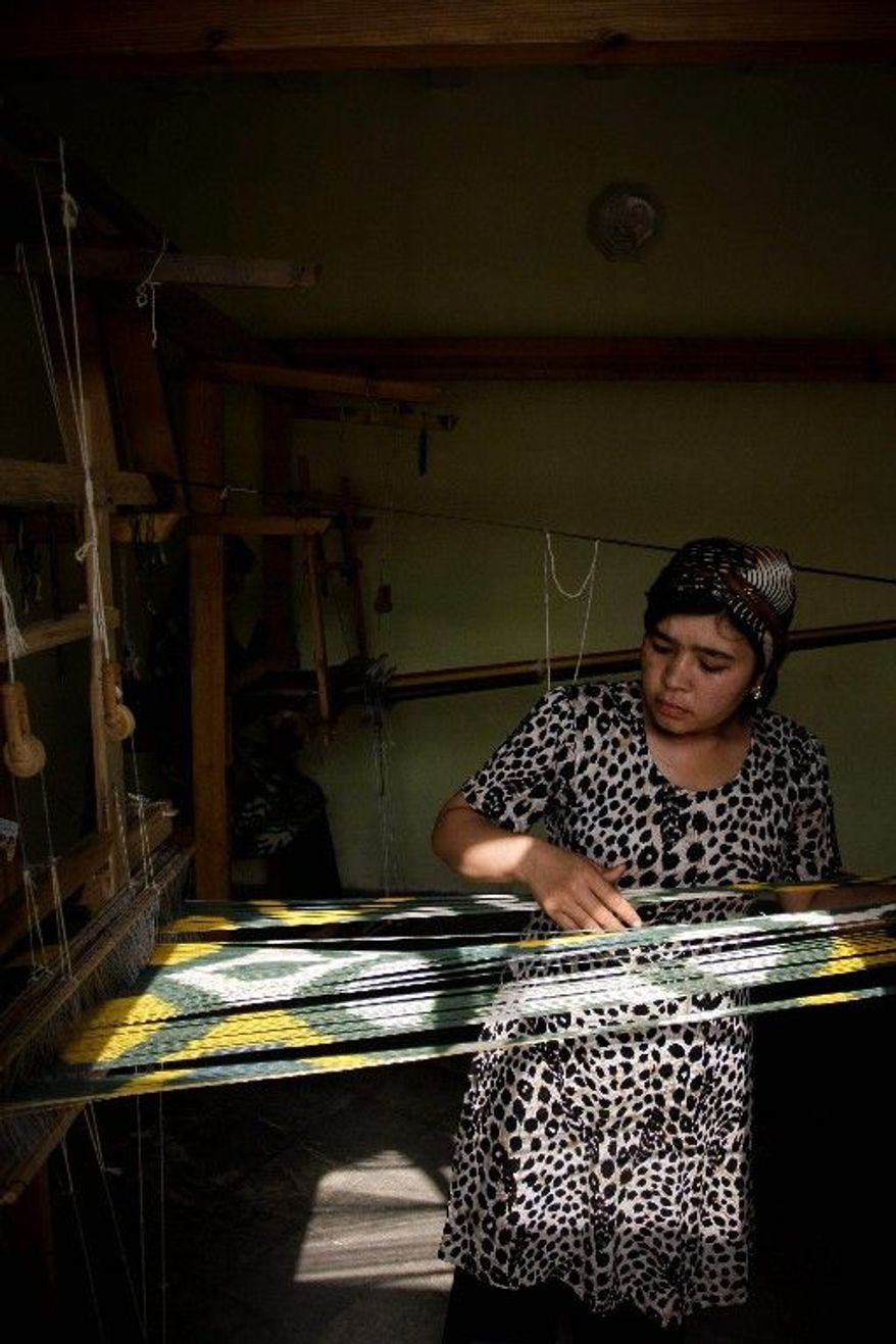 An Uzbek woman weaves silk in a workshop in Margilan. Children miss school in silk season and work from pre-dawn to midnight.
