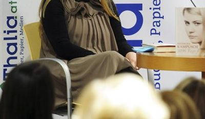 """Natascha Kampusch poses with her book """"3,096 Tage"""" (3,096 Days) during a presentation at a book store in Vienna, Austria, on Thursday, Sept. 9, 2010. Kampusch, who was kidnapped at age 10 says she was repeatedly beaten, starved and forced to do housework half-naked during her 8 1/2 years at the mercy of a man who admired Hitler and considered himself an Egyptian god. (AP Photo/Hans Punz)"""