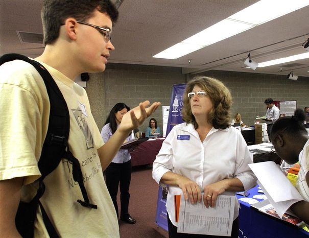 In this Aug. 26, 2010, photograph, University of Illinois at Springfield Career Counselor Gail Kilbury, right, speaks with students seeking employment, during a University of Illinois Job Fair in Springfield, Ill. Even though the economy is growing more slowly, companies in recent weeks are resisting making even deeper cuts to their work forces. (AP Photo/Seth Perlman)