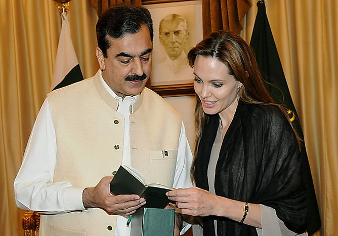 In this photo taken on Wednesday, Sept. 8, 2008, provided by Pakistan's Press Information Department, Pakistan's Prime Minister Yousuf Raza Gilani, left, presents a copy of a Quran to UNHCR Goodwill Ambassador, U.S. actress Angelina Jolie in Islamabad, Pakistan. Jolie on Wednesday condemned a Florida church's threat to burn copies of the Muslim holy book to mark the ninth anniversary of the Sept. 11 attacks. (AP Photo/Press Information Department)