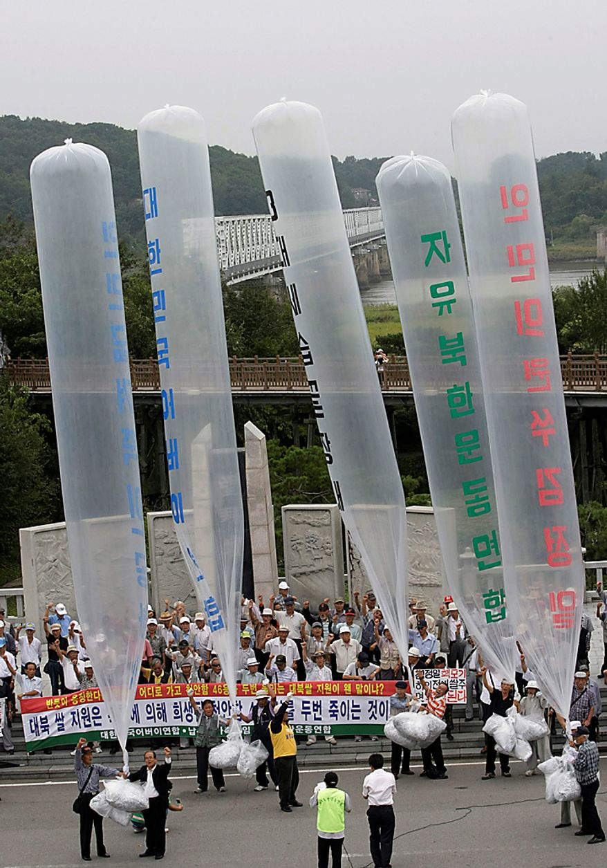 "Defectors from North Korea and conservative activists release balloons with leaflets condemning North Korean leader Kim Jong Il at the Imjingak Pavilion near the border village of Panmunjom, the demilitarized zone which has separated the two Koreas since the Korean War, in Paju, South Korea, Thursday, Sept. 9, 2010. North Korea celebrated its 62nd anniversary Thursday with odes to supreme leader Kim and pilgrimages to his late father's statue amid suggestions that a political meeting believed aimed at promoting his son as successor is imminent. The writing on the balloons reads ""Overthrow Kim Jong Il's dictatorship."" (AP Photo/Ahn Young-joon))"