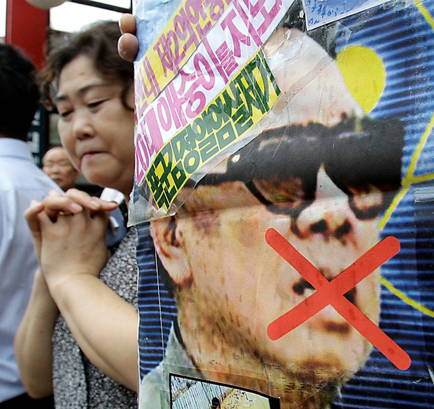 A woman reacts near a picture of North Korea leader Kim Jong Il during a rally held against pro-North Korean groups in Seoul, South Korea, Thursday, Sept. 9, 2010. The youngest son of Kim Jong Il is widely expected to make his public debut as the Dear Leader's heir apparent at a rare Workers' Party convention, the nation's biggest political gathering in 30 years. (AP Photo/ Lee Jin-man)