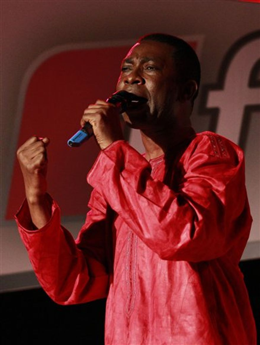 In this Wednesday, Sept. 1, 2010 photo, Senegalese pop star Youssou Ndour gestures during the launch of his television station, TFM, in Dakar, Senegal. Outside of Senegal, the 50-year-old chart-topping artist is best-known for his grooving mbalax beat. In his native country, he is also known for his scathing critique of the ruling party. Senegal's government has forbidden Ndour from doing newscasts on his new channel, and the license allowing him to do 'cultural programming' was only granted after a two-year stalemate. (AP Photo/Rebecca Blackwell)
