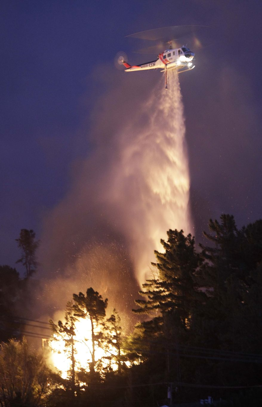 A helicopter drops water on a massive fire through a mostly residential neighborhood in San Bruno, Calif., Thursday, Sept. 9, 2010. Firefighters from San Bruno and surrounding cities are battling the blaze that started on a hillside and is now consuming homes the San Francisco suburb. (AP Photo/Paul Sakuma)
