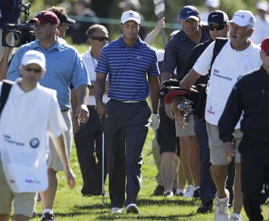 Tiger Woods checks his ball in the fourth rough before his second shot during the final round at the BMW Championship golf tournament in Lemont, Ill., Sunday, Sept. 12, 2010. (AP Photo/Nam Y. Huh)