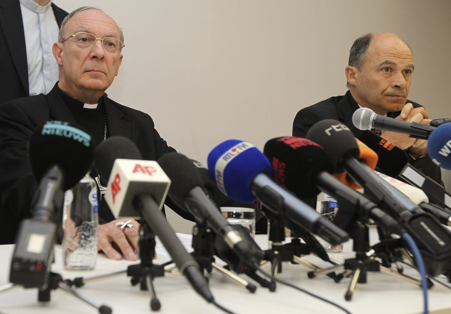 In this April 23, 2010 file photo, Belgium's Archbishop Andre-Joseph Leonard, left, and commission chairman Peter Adriaenssens address the media in Brussels about the sexually abuse of a Bishop. A Belgian commission looking into sexual abuse by Catholic clergy says it has received testimony from hundreds of victims and that witnesses say widespread abuse over decades led to at least 13 suicides. (AP Photo/Yves Logghe, file)