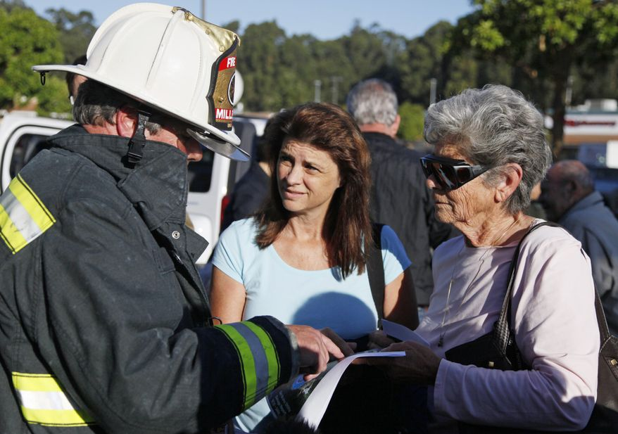 Millbrae, Calif., fire chief Dennis Haage, left, talks with San Bruno, Calif., residents Toni Vaccari, right, and her daughter, Debbie Shea, about returning to their homes near last night's gas explosion following a press conference, Friday, Sept. 10, 2010, at a shopping center in San Bruno. (AP Photo/Eric Risberg)