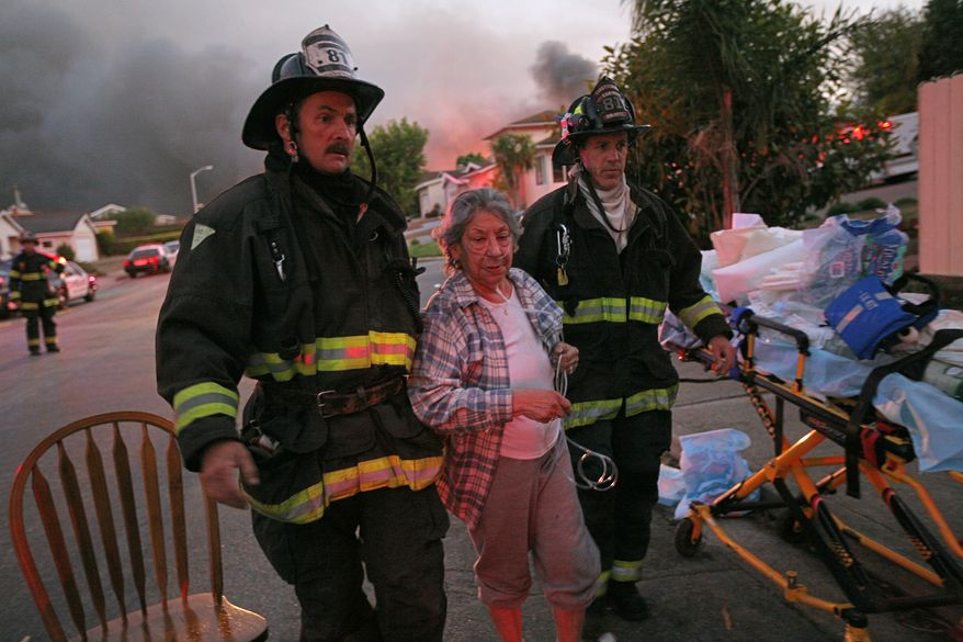 A woman is treated by firemen after an explosion in San Bruno, Calif., Thursday, Sept. 9, 2010. Several homes were destroyed as a massive fire roared through a mostly residential neighborhood in San Bruno. (AP Photo/Mike Adaskaveg)