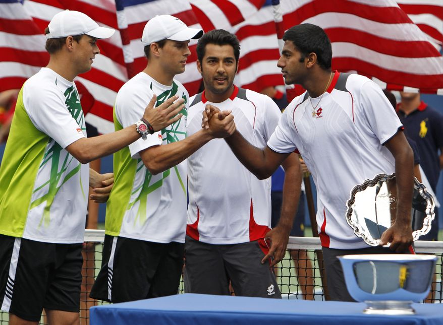 Rohan Bopanna of India, right, shakes hands with Mike Bryan, second from left, of the United States after Bryan and his brother Bob Bryan, left, beat Bopanna and partner Aisam-Ul-Haq Qureshi of Pakistan in the men's doubles final at the U.S. Open tennis tournament in New York, Friday, Sept. 10, 2010. The Bryan brothers won the match 7-6(5), 7-6(4). (AP Photo/Paul J. Bereswill)