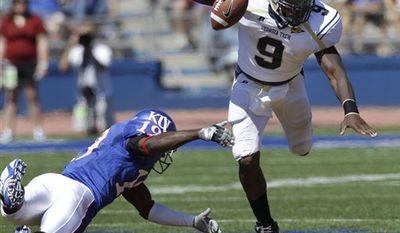 Georgia Tech quarterback Joshua Nesbitt (9) is tripped up by Kansas cornerback Isiah Barfield (19) during the second half of their NCAA college football game in Lawrence, Kan., Saturday, Sept. 11, 2010. Kansas defeated Georgia Tech 28-25. (AP Photo/Orlin Wagner)
