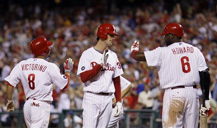 Philadelphia Phillies first base coach  Davey Lopes, right, checks on Jimmy Rollins after Rollins' hit a double in the third inning of a baseball game against the Florida Marlins, Wednesday, Sept. 8, 2010, in Philadelphia. Rollins left after the inning with tightness in his right hamstring. Philadelphia won 10-6. (AP Photo/Matt Slocum)