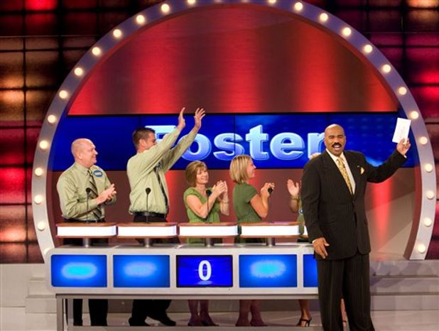 """In this publicity image released by FremantleMedia N.A., host Steve Harvey, is shown with the Foster family during a taping of the game show, """"Family Feud."""" (AP Photo/FremantleMedia N.A.)"""
