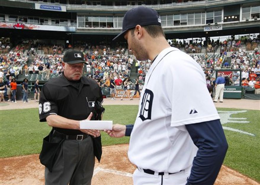 FILE - In this June 3, 2010, file photo, Detroit Tigers pitcher Armando Galarraga, right, hands the lineup card umpire Jim Joyce before the Detroit Tigers-Cleveland Indians MLB baseball game in Detroit. Galarraga is the probable pitcher and Joyce is scheduled to be behind the plate Friday night, Sept. 10, 2010, when Detroit hosts the Baltimore Orioles. (AP Photo/Paul Sancya, File)