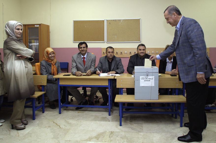 Turkish Prime Minister Recep Tayyip Erdogan casts his vote in Istanbul on Sunday, Sept. 12, 2010, in a referendum on changes to the Turkish Constitution, which was crafted in the wake of Turkey's 1980 military coup. His wife, Emine Erdogan, is at left. (AP Photo/Ibrahim Usta)