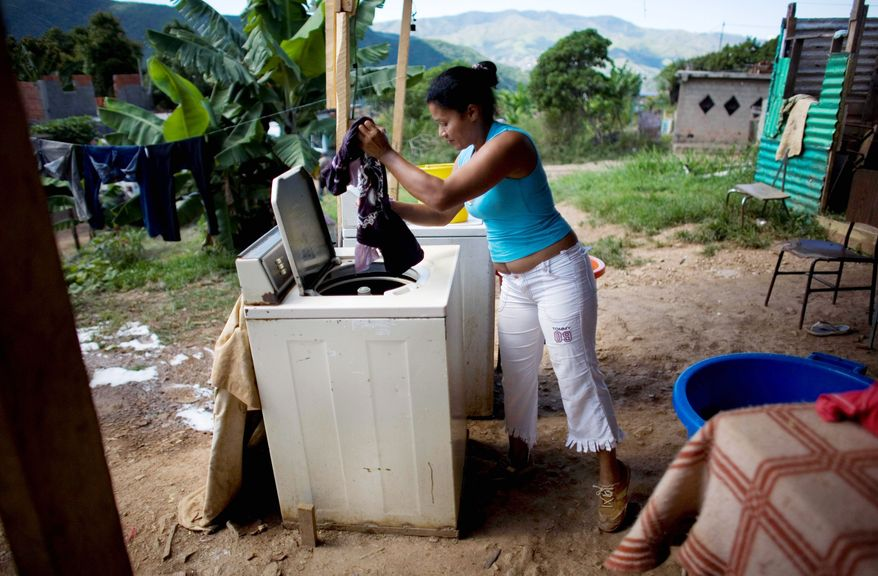 Fidela Hernandez, 46, uses a washing machine last month after filling it with water, bucket by bucket, in La Pedrera, one of the most impoverished slums in Caracas, Venezuela. The slums have been growing, driven largely by migration of people from depressed rural areas to Caracas. (Associated Press)