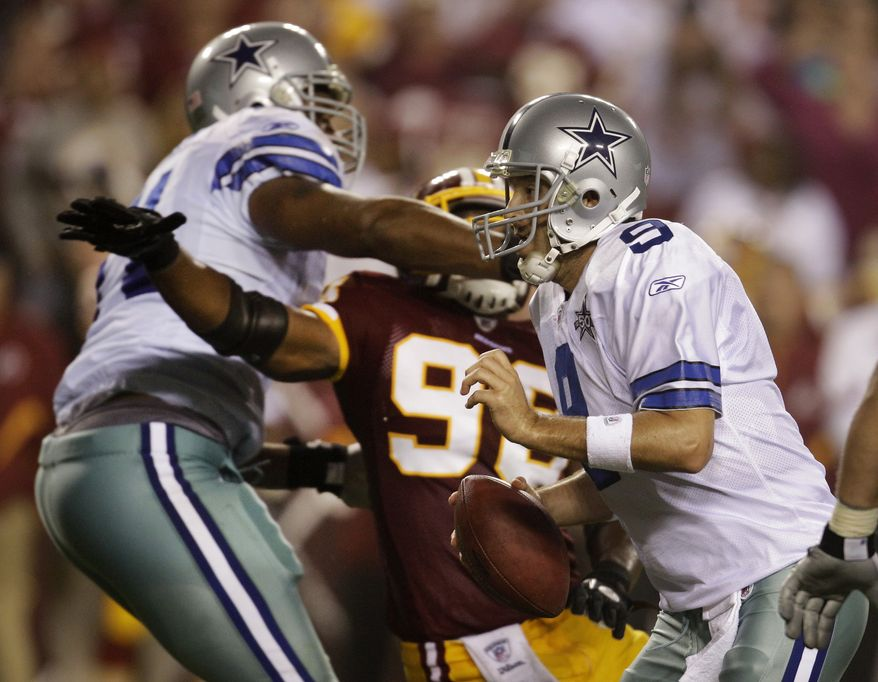 Dallas Cowboys quarterback Tony Romo (9) scrambles on the last play of the game as offensive tackle Alex Barron (left) holds Washington Redskins linebacker Brian Orakpo during the Redskins' 13-7 victory Sunday in Landover, Md. Offensive tackle Barron's penalty negated a Cowboys touchdown in the last seconds of the game. (Associated Press)