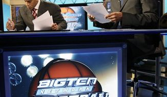 FILE - This Feb. 5, 2010, file photo shows Big Ten Network college basketball commentators Dave Revsine, left, Jim Jackson, center, and Steve Smith preparing for the network's basketball show in Chicago. The Big Ten Network introduced itself to skeptics in 2007, and its earliest programming did little to ease that skepticism. But three years later the not-so-little cable network is delivering tens of millions of dollars to the conference it exists to serve, and it is clearly the model for _ and some might say the envy of _ big-time college sports around the country. (AP Photo/Charles Rex Arbogast, File)