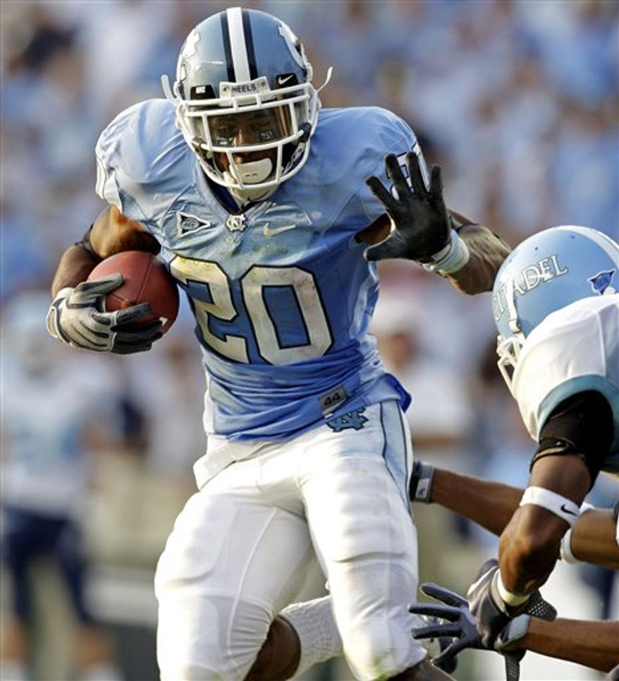 FILE -- This Sept. 5, 2010, file photo shows North Carolina's Shaun Draughn (20) running the football as Citadel defenders try to tackle him during the first half of an NCAA college football game in Chapel Hill, N.C.  Draughn will return for this weekend's game against Georgia Tech after sitting out a game due to the ongoing NCAA investigation. (AP Photo/Gerry Broome, File)
