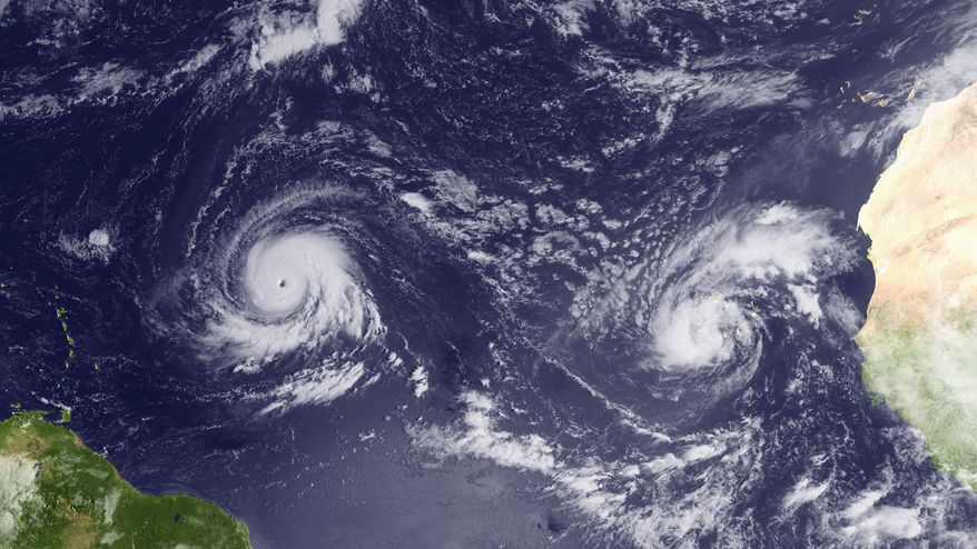 This Monday Sept. 13, 2010, satellite image provided by NOAA shows Hurricane Igor, left, east of the Northern Leeward Islands and Tropical Storm Julia, right, south-southwest of the Cape Verde Islands. Igor threatened to become a Category 5 storm Monday as it churned far out over the Atlantic Ocean. (AP Photo/NOAA)