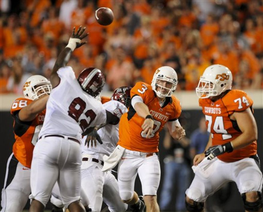 Troy teammates, defensive end Mario Addison (7) and defensive back Jimmie Anderson (19), cause a fumble while sacking Oklahoma State quarterback Brandon Weeden (3) during the first half of an NCAA college football game in Stillwater, Okla. Saturday, Sept. 11, 2010. (AP Photo/Brody Schmidt)