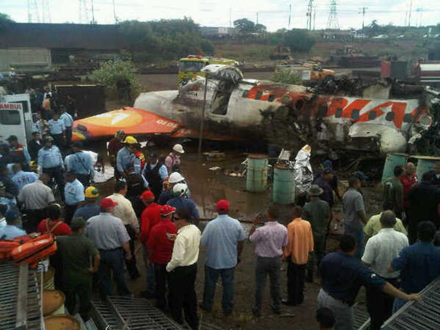 In this image courtesy of Globovision Television News, people surrounds the wreckage of an airplane of a state airline Conviasa after it crashed about 6 miles from the eastern city of Puerto Ordaz, Venezuela, Monday, Sept. 13, 2010. The plane was carrying 51 people, and officials said at least 33 people survived.(AP Photo/Globovison)