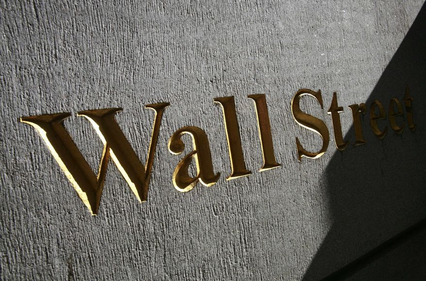 March 8, 2010, file photograph of a sign for Wall Street near the New York Stock Exchange. Stock futures are rising sharply Monday, Sept. 13, as investors gain confidence in the banking sector following the passage of new global regulations and China's economy continues its robust growth. (AP Photo/Mark Lennihan, file)