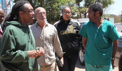 American doctors, from left, Gregory Reinard, David Greenburg, Gloria Cox Cronwell and Anthony Eugene Jones appear at the magistrates courts in Harare, Zimbabwe Monday, Sept. 13, 2010. The four, charged under Zimbabwean laws for practising medicine and selling drugs without a license, were released on bail after paying $200 each and could face a fine and deportation. (AP Photo/Tsvangirayi Mukwazhi)