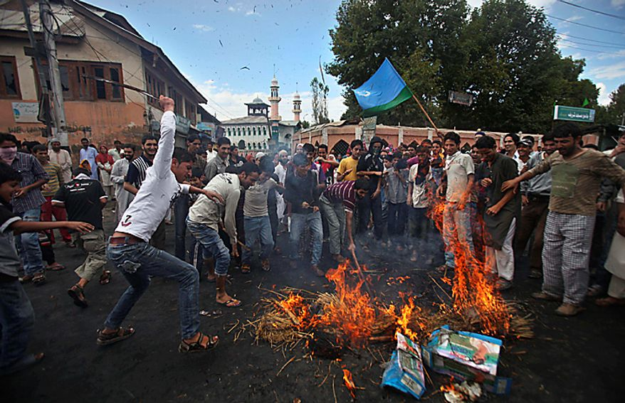 Kashmiri protesters beat the remains of an effigy of U.S. President Barack Obama after burning it during a protest in Srinagar, India, Monday, Sept. 13, 2010. Indian forces battled Kashmiri protesters in the streets of the disputed territory Monday in demonstrations fueled in part by a report of the Quran being desecrated in the United States. (AP Photo/Altaf Qadri)
