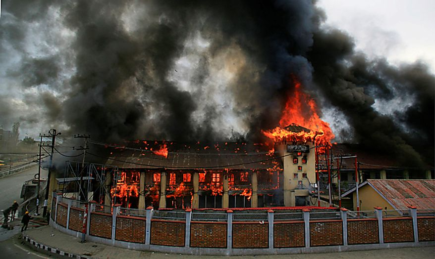 Firefighters try to douse flames at a government building set on fire by protesters in Srinagar, India, Saturday, Sept. 11, 2010. Police fired warning shots and tear gas to disperse hundreds of demonstrators who attacked a police post and burned government offices in Kashmir on Saturday, as tens of thousands of people took to the streets to protest Indian rule in the Himalayan region, officials said. (AP Photo/Altaf Qadri)