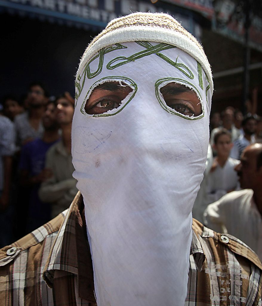 A masked Kashmiri protestor looks on during a protest rally after Eid al-Fitr prayers in Srinagar, India, Saturday, Sept. 11, 2010. Police fired warning shots and tear gas to disperse hundreds of demonstrators who attacked a police post and burned government offices in Kashmir on Saturday, as tens of thousands of people took to the streets to protest Indian rule in the Himalayan region, officials said. (AP Photo/Altaf Qadri)