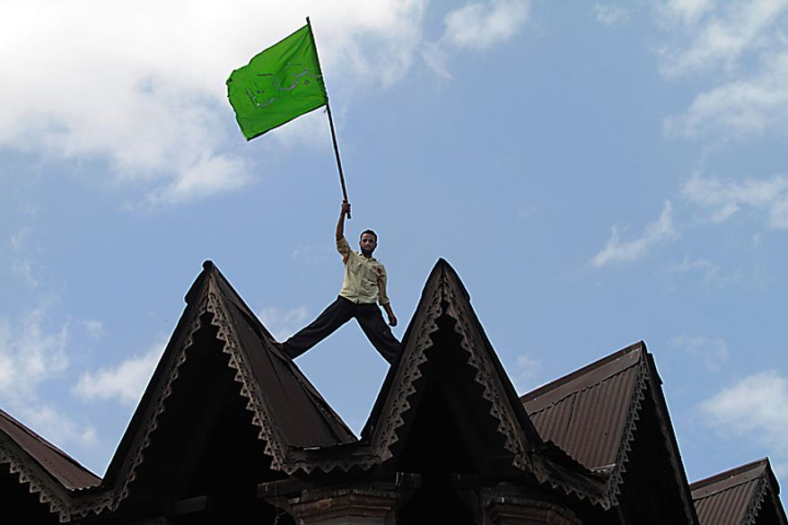 A Kashmiri Muslim protester waves an Islamic flag standing on top of a building during a protest rally after Eid al-Fitr prayers in Srinagar, India, Saturday, Sept. 11, 2010. Police fired warning shots and tear gas to disperse hundreds of demonstrators who attacked a police post and burned government offices in Kashmir on Saturday, as tens of thousands of people took to the streets to protest Indian rule in the Himalayan region, officials said. (AP Photo/Dar Yasin)