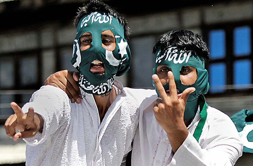"Masked Kashmiri protesters display the victory sign during a protest rally after Eid al-Fitr prayers in Srinagar, India, Saturday, Sept. 11, 2010. Police fired warning shots and tear gas to disperse hundreds of demonstrators who attacked a police post and burned government offices in Kashmir on Saturday, as tens of thousands of people took to the streets to protest Indian rule in the Himalayan region, officials said. Scarf reads ""Allah is great,"" top, and ""There is no God but Allah and Prophet Mohammad is his messenger,"" bottom. (AP Photo/Dar Yasin)"