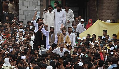 Key separatist leader Mirwaiz Umar Farooq, seated center atop car, and Jammu and Kashmir Liberation Front leader Yasin Malik, seated front left, gesture to the crowd during a protest in Srinagar, India, Friday, Sept. 10, 2010. In an attempt to forge unity among separatists in Jammu and Kashmir, Malik and Farooq offered Friday prayers together, the first time the leaders have shared public space since September 2003 when the then Hurriyat Conference split, according to a news agency. (AP Photo/Mukhtar Khan)
