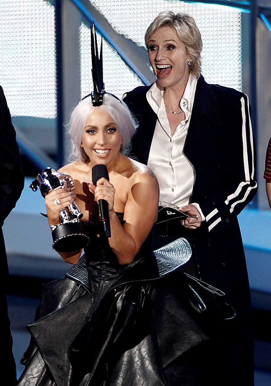 """Lady Gaga accepts the award for best pop video for """"Bad Romance"""" at the MTV Video Music Awards on Sunday, Sept. 12, 2010 in Los Angeles. In background is presenter Jane Lynch, of the cast of Glee. (AP Photo/Matt Sayles)"""