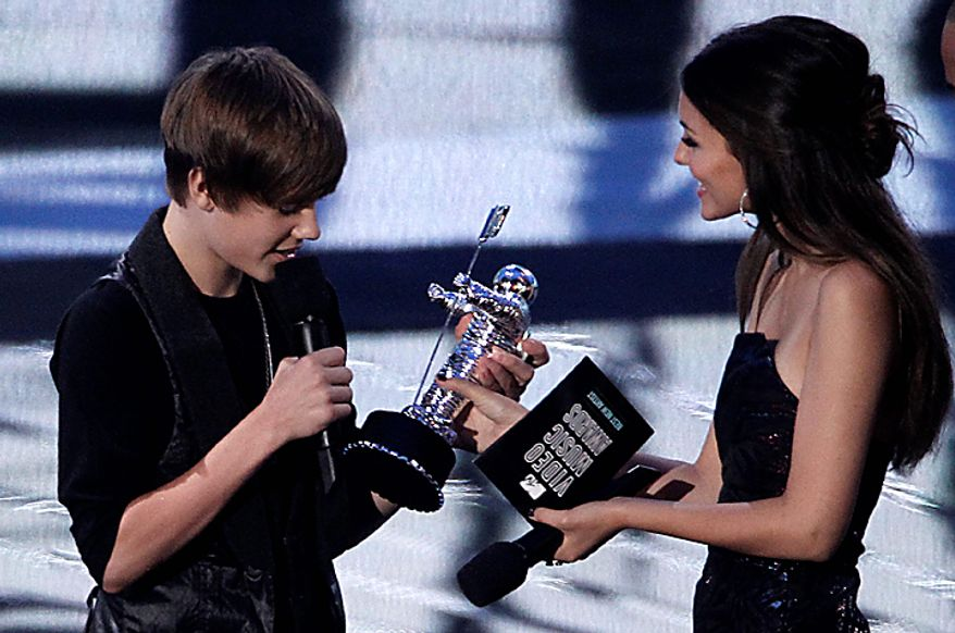 Justin Bieber accepts the best new artist award from presenter Victoria Justice at the MTV Video Music Awards on Sunday, Sept. 12, 2010 in Los Angeles. (AP Photo/Matt Sayles)
