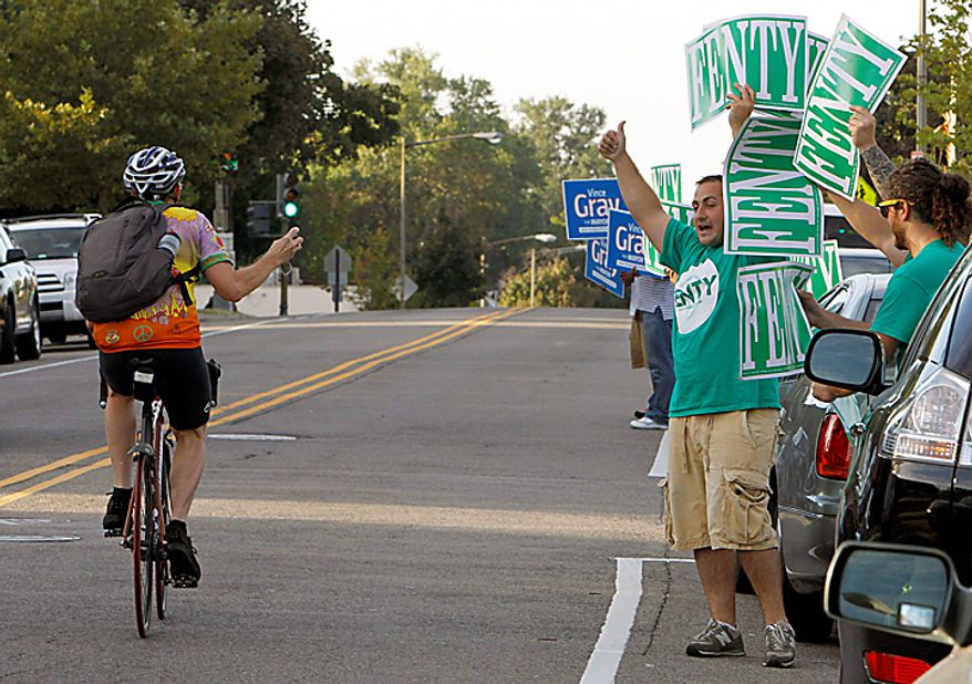 Adrian Fenty and Vince Gray volunteers cheer at a passing bicyclist outside a polling place in Washington,  Tuesday,  Sept. 14, 2010, as voters cast their ballots in the District of Columbia primaries.  (AP Photo/Ann Heisenfelt)