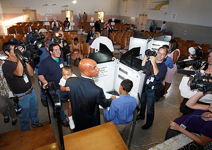 Washington Mayor Adrian Fenty is surrounded by cameras as he casts his vote in Washington,  Tuesday,  Sept. 14, 2010, as Washington held its mayoral primary.  (AP Photo/Ann Heisenfelt)