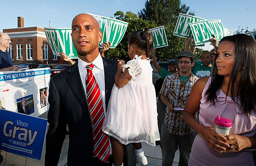 Washington Mayor Adrian Fenty, left, arrives with his wife, Michelle, and carries daughter, Aerin, as he prepares to vote in Washington,  Tuesday,  Sept. 14, 2010, as Washington held its mayoral primary.  (AP Photo/Ann Heisenfelt)
