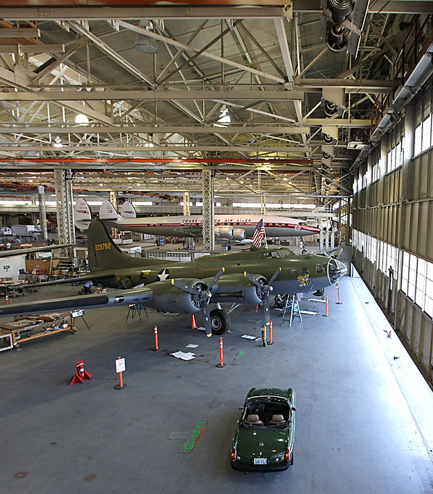 """In this photo taken July 14, 2010, a Boeing B-17F Flying Fortress that is undergoing restoration is parked in front of the massive doors of the Boeing Co.'s historic """"Plant 2,"""" in Seattle. After giving birth to some of the world's most significant aircraft, the outdated facility is scheduled to be torn down this fall. Behind the B-17 is a restored Lockheed Super Constellation airliner. (AP Photo/Ted S. Warren)"""