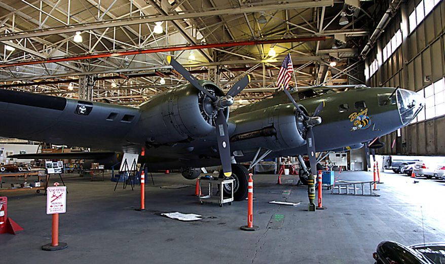 """In this July 14, 2010 photo, a Boeing B-17F Flying Fortress that is undergoing restoration is parked in front of the massive doors of the Boeing Co.'s historic """"Plant 2,"""" in Seattle. After giving birth to some of the world's most significant aircraft, the outdated facility is scheduled to be torn down this fall. (AP Photo/Ted S. Warren)"""