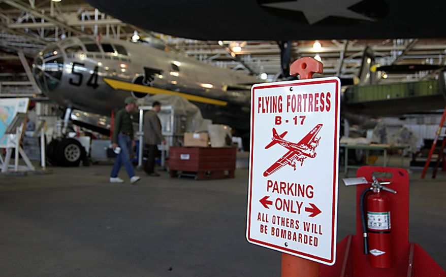 """In this photo taken July 14, 2010, a parking sign referencing the Boeing B-17 Flying Fortress with a silver B-29 in the background is shown at the Boeing Co.'s historic """"Plant 2,"""" in Seattle. After giving birth to some of the world's most significant aircraft, the outdated facility is scheduled to be torn down this fall. (AP Photo/Ted S. Warren)"""