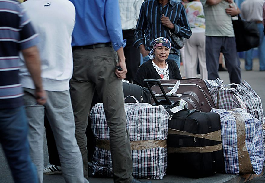 """A Romanian Roma woman sits by luggage, after she and more than 200 others arrived on two special flights from France, in Bucharest, Romania, Tuesday, Sept. 14, 2010. France's deportations of Gypsies are """"a disgrace"""" and probably break EU law, the European Union's executive body declared Tuesday in a stinging rebuke that set up a showdown with French President Nicolas Sarkozy's conservative government. (AP Photo/Vadim Ghirda)"""