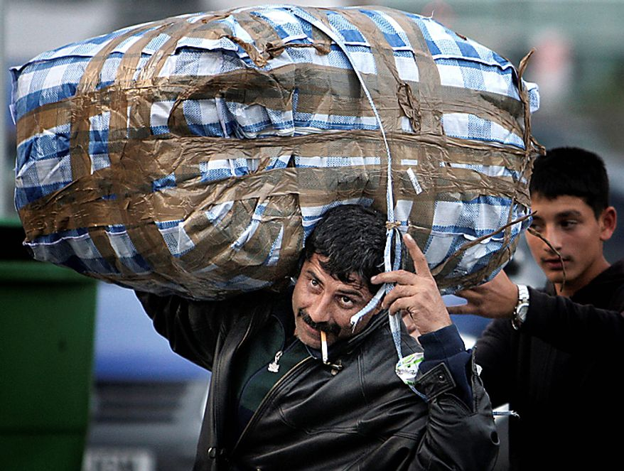 """A Romanian Roma man carries a large bag, after he and more than 200 others arrived on two special flights from France, in Bucharest, Romania, Tuesday, Sept. 14, 2010. France's deportations of Gypsies are """"a disgrace"""" and probably break EU law, the European Union's executive body declared Tuesday in a stinging rebuke that set up a showdown with French President Nicolas Sarkozy's conservative government. (AP Photo/Vadim Ghirda)"""