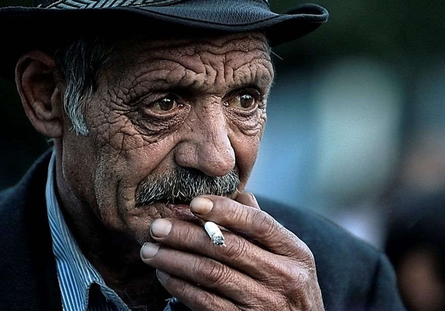 """An elderly Romanian Roma man smokes after he and more than  200 others arrived on two special flights from France, in Bucharest, Romania, Tuesday, Sept. 14, 2010. France's deportations of Gypsies are """"a disgrace"""" and probably break EU law, the European Union's executive body declared Tuesday in a stinging rebuke that set up a showdown with French President Nicolas Sarkozy's conservative government. (AP Photo/Vadim Ghirda)"""